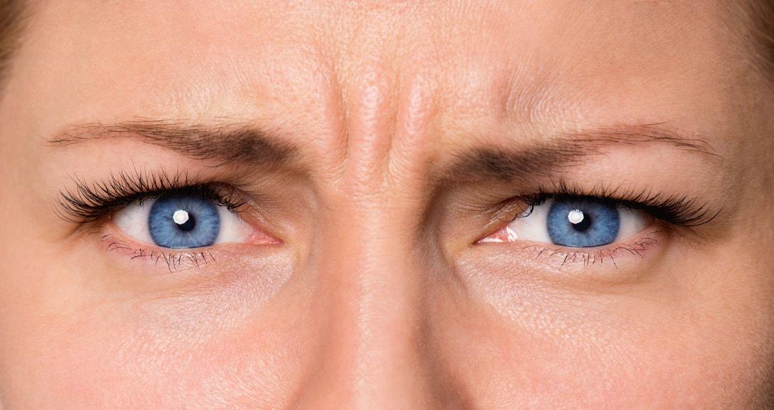 Bild einer Frau mit strengem Blick und einer Zornesfalte.